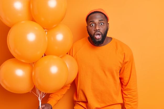 Jonge, bebaarde zwarte bebaarde man kijkt geschokt houdt mond open van verbazing en ongeloof draagt oranje hoed en trui poses met helium ballonnen komt op feestje geïsoleerd binnen