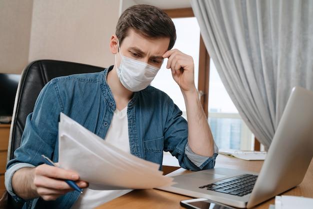 Jonge, bedachtzame man met beschermend gezichtsmasker studeert en werkt op afstand vanwege coronavirus of covid-19 quarantaine