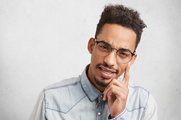 Jonge bedachtzame onderzoeker met donkere huid draagt een grote bril, houdt de vinger op de slaap