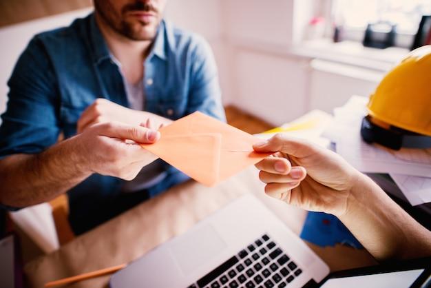 Jonge bedorven ondernemersmens die steekpenningen in de envelop ontvangt. concept corruptie voor illegale deals op kantoor.