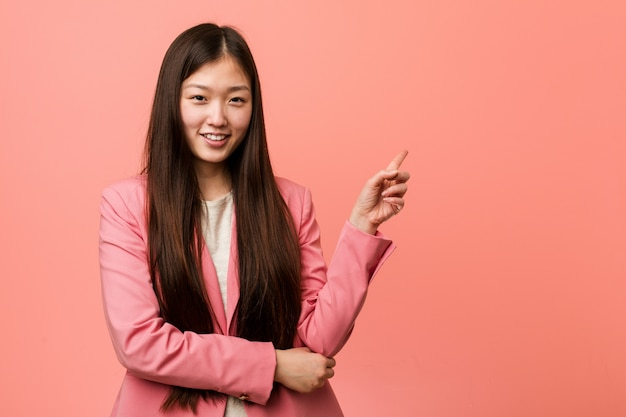 Jonge bedrijf chinese vrouw die het roze kostuum glimlachen dragen die cheerfully wijs met wijsvinger weg wijzen.