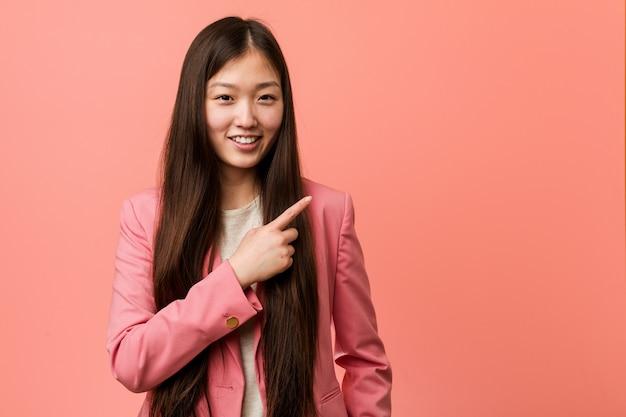 Jonge bedrijf chinese vrouw die roze en kostuums draagt die opzij glimlachen richten, die iets tonen bij lege ruimte.