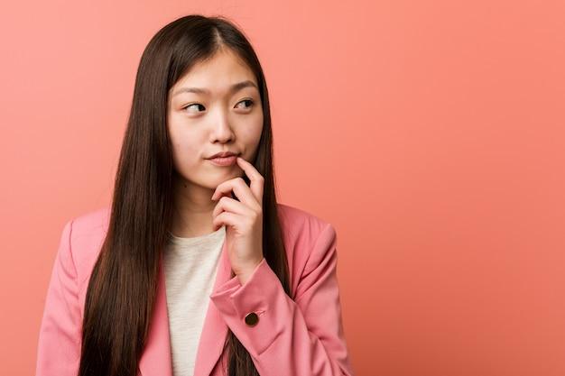 Jonge bedrijf chinese vrouw die roze kostuum draagt dat zijdelings met twijfelachtige en sceptische uitdrukking kijkt.