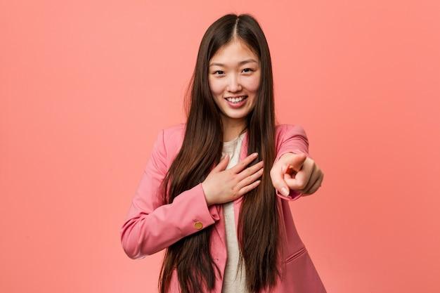 Jonge bedrijf chinese vrouw, gekleed in roze pak punten met duim vinger weg, lachen en zorgeloos.
