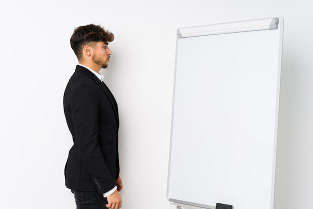 Jonge bedrijf coaching arabische man staren naar links, zijwaarts poseren.