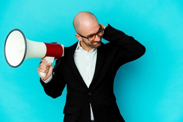 Jonge bedrijf kale man met een megafoon geïsoleerd achterhoofd aanraken, denken en een keuze maken.