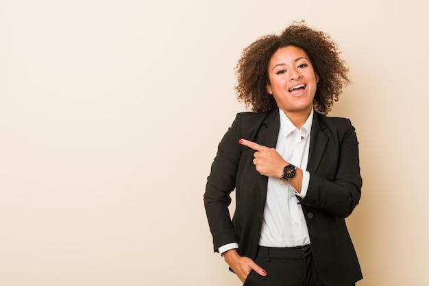 Jonge bedrijfs afrikaanse amerikaanse en vrouw die opzij glimlacht richt, die iets toont op lege ruimte.