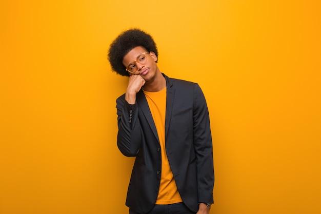 Jonge bedrijfs afrikaanse amerikaanse mens over een oranje muur die aan iets denkt, kijkend aan de kant