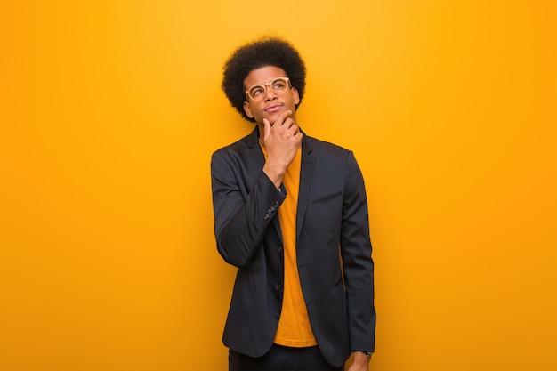 Jonge bedrijfs afrikaanse amerikaanse mens over een oranje muur die en verward twijfelen
