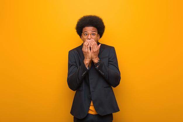 Jonge bedrijfs afrikaanse amerikaanse mens over een oranje muur zeer sca en bang verborgen