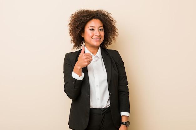 Jonge bedrijfs afrikaanse amerikaanse vrouw die en duim omhoog glimlachen opheffen