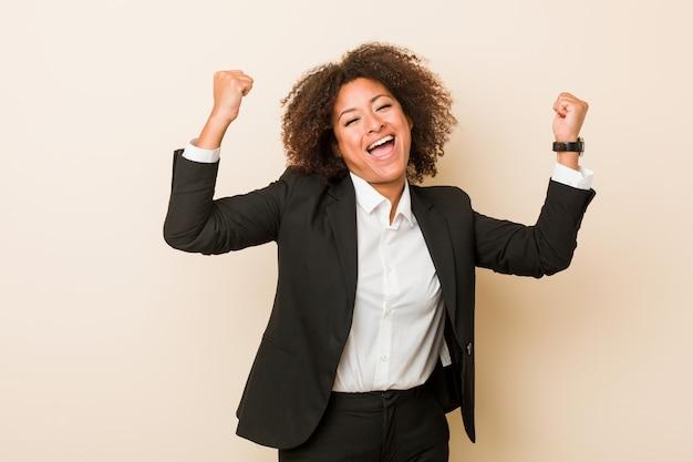 Jonge bedrijfs afrikaanse amerikaanse vrouw die sterktegebaar met wapens, symbool van vrouwelijke macht toont