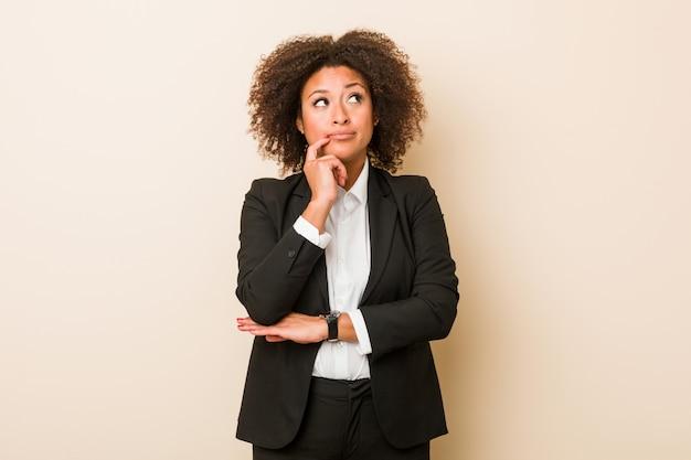 Jonge bedrijfs afrikaanse amerikaanse vrouw die zijdelings met twijfelachtige en sceptische uitdrukking kijkt.