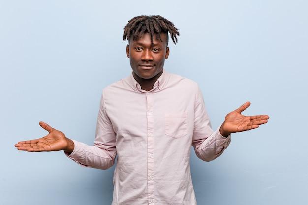 Jonge bedrijfs afrikaanse zwarte mens die een welkom uitdrukking toont.