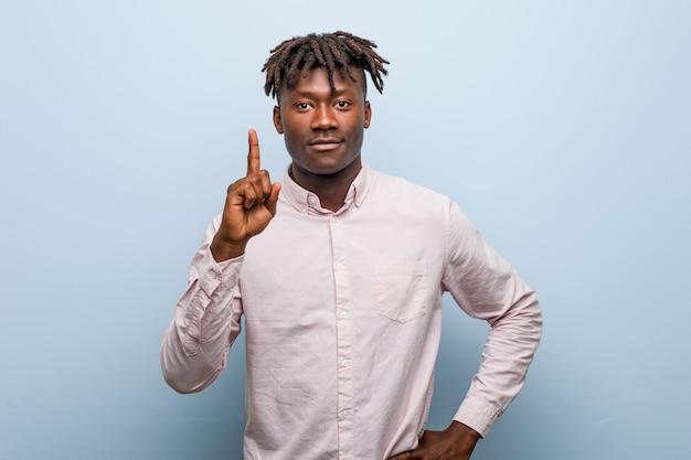 Jonge bedrijfs afrikaanse zwarte mens die nummer één met vinger toont.