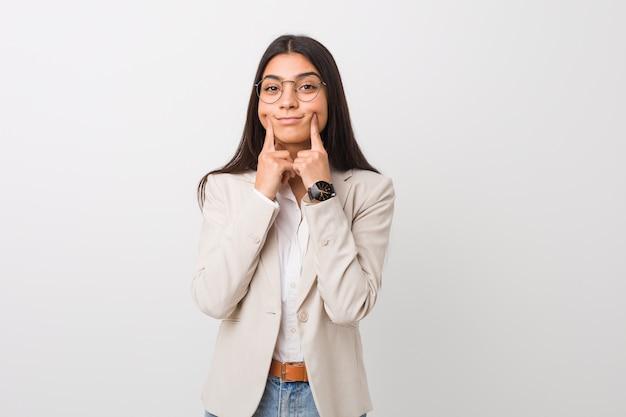 Jonge bedrijfs arabische vrouw die tegen een wit wordt geïsoleerd dat tussen twee opties twijfelt.
