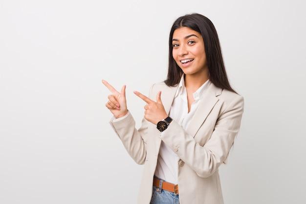 Jonge bedrijfs arabische vrouw die tegen het witte richten wordt geïsoleerd die met forefingersa richt, opwinding en wens uitdrukt.