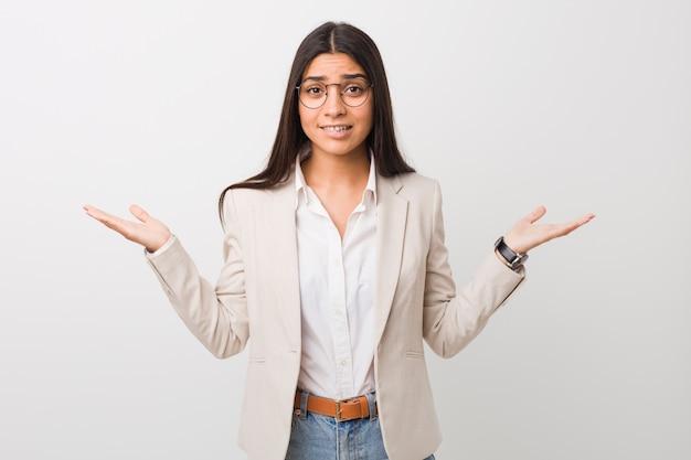 Jonge bedrijfs arabische vrouw die tegen witte verwarde en twijfelachtige schouders wordt geïsoleerd om een exemplaarruimte te houden.