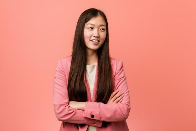 Jonge bedrijfs chinese vrouw die het roze kostuum glimlachen draagt zeker met gekruiste wapens.
