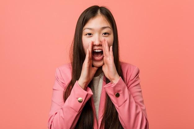 Jonge bedrijfs chinese vrouw die het roze kostuum schreeuwen opgewekt aan voorzijde draagt.