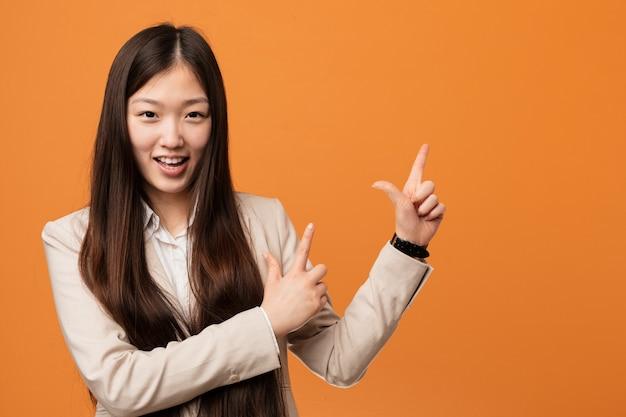 Jonge bedrijfs chinese vrouw die met wijsvingers aan een exemplaarruimte richt, die opwinding en wens uitdrukt.