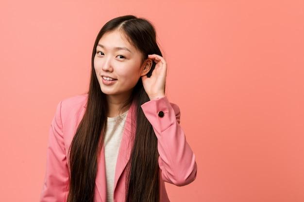 Jonge bedrijfs chinese vrouw die roze kostuum draagt dat aan een roddel probeert te luisteren.