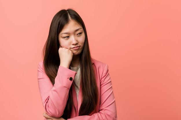 Jonge bedrijfs chinese vrouw die roze kostuum draagt dat droevig en nadenkend voelt, bekijkend exemplaarruimte.