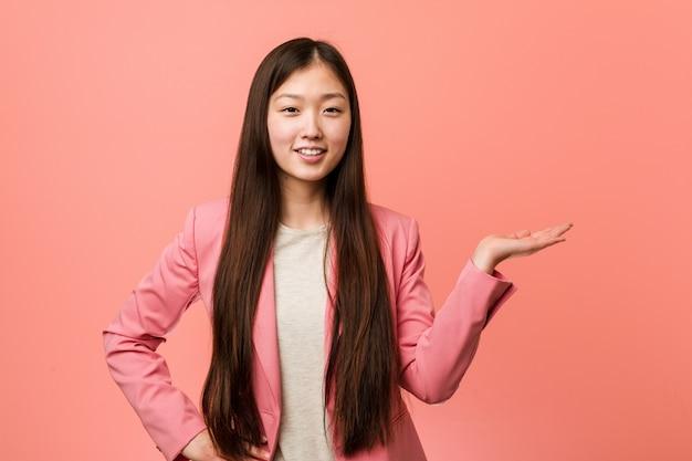 Jonge bedrijfs chinese vrouw die roze kostuum draagt dat een exemplaarruimte op een palm toont en een andere hand op taille houdt.