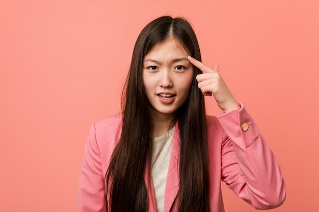 Jonge bedrijfs chinese vrouw die roze kostuum draagt dat een teleurstellingsgebaar met wijsvinger toont.