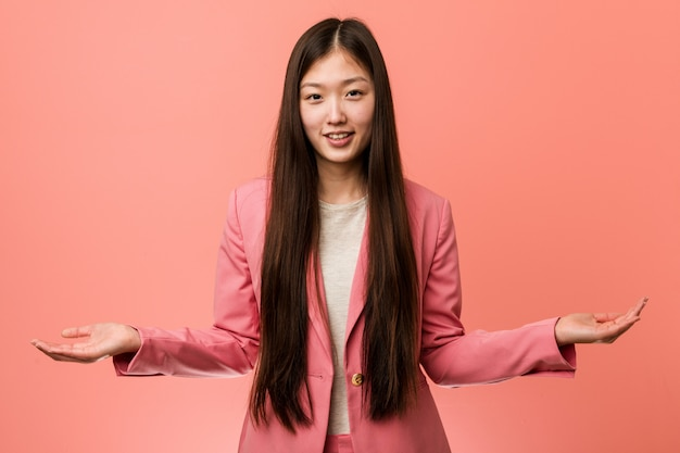 Jonge bedrijfs chinese vrouw die roze kostuum draagt dat een welkome uitdrukking toont.