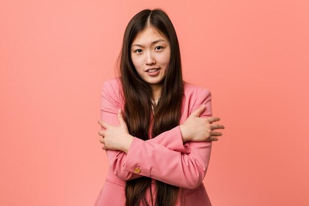 Jonge bedrijfs chinese vrouw die roze kostuum draagt dat koud wegens lage temperatuur of een ziekte gaat.