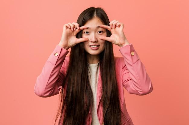 Jonge bedrijfs chinese vrouw die roze kostuum draagt dat ogen houdt geopend om een succeskans te vinden.