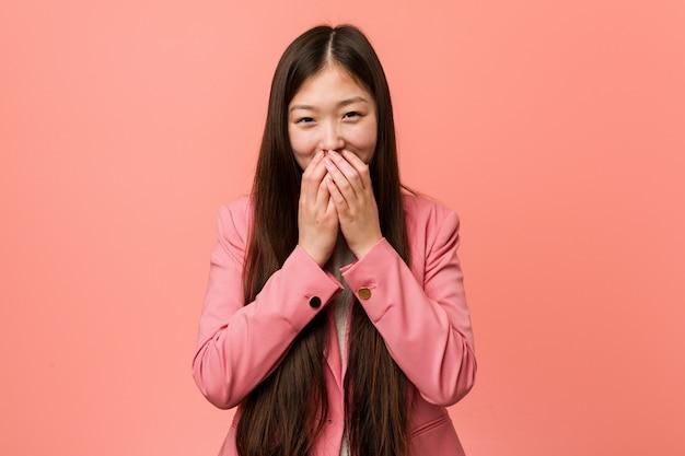 Jonge bedrijfs chinese vrouw die roze kostuum draagt dat over iets lacht, die mond behandelt met handen.
