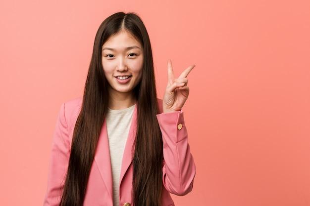 Jonge bedrijfs chinese vrouw die roze kostuum draagt dat overwinningsteken toont en breed glimlacht.