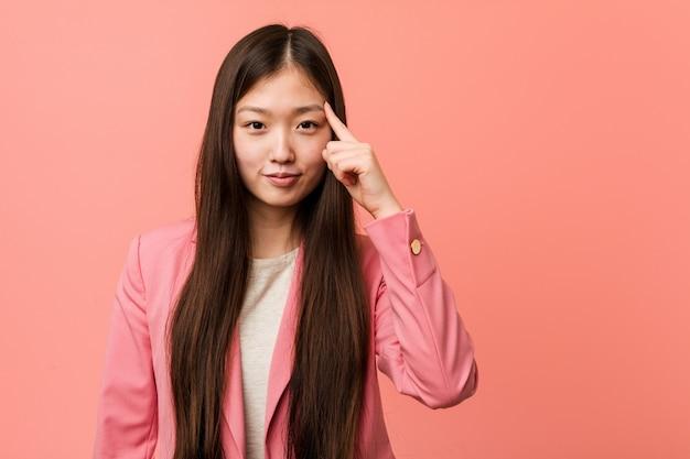 Jonge bedrijfs chinese vrouw die roze kostuum draagt dat tempel met vinger richt, denkt, geconcentreerd op een taak.