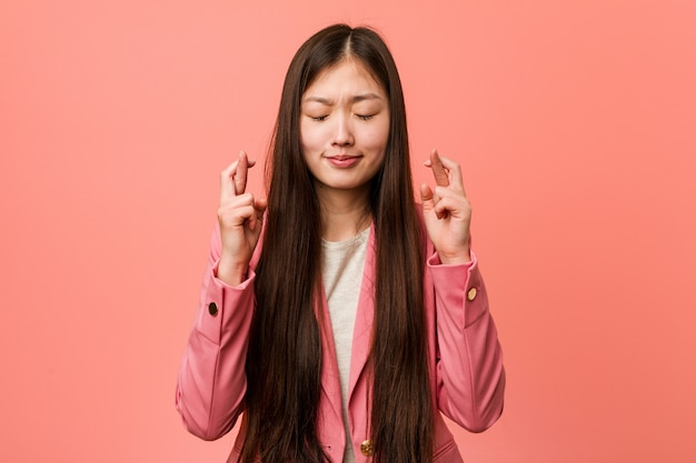 Jonge bedrijfs chinese vrouw die roze kostuum draagt dat vingers kruist voor het hebben van geluk