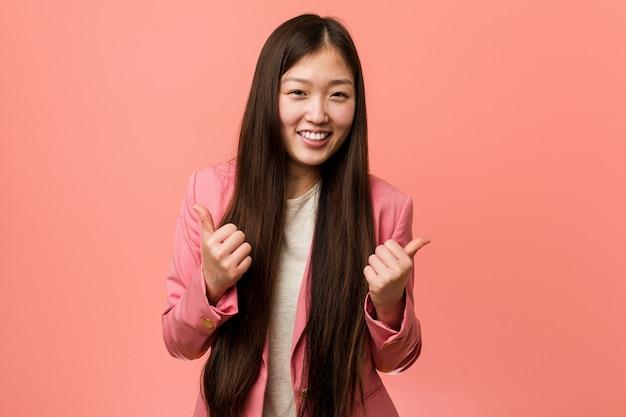 Jonge bedrijfs chinese vrouw die roze kostuum draagt die beide duimen omhoog, glimlachend en zeker opheft.