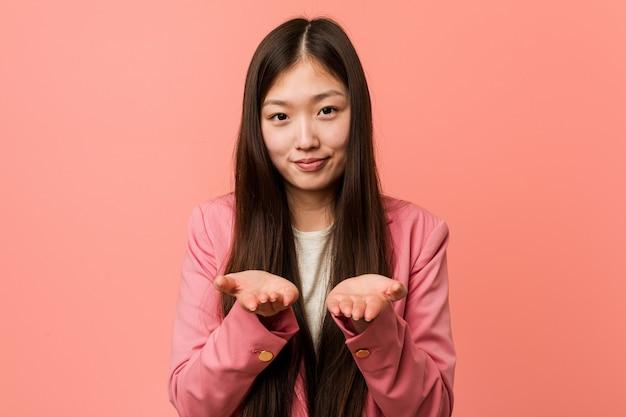 Jonge bedrijfs chinese vrouw die roze kostuumholding iets met palmen draagt, die aan camera aanbieden.