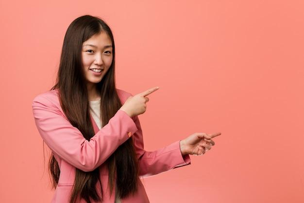 Jonge bedrijfs chinese vrouw die roze opgewekt kostuum draagt richt met weg wijsvingers.