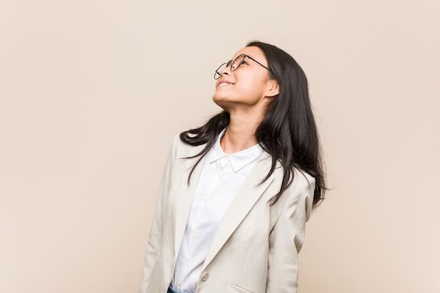 Jonge bedrijfs chinese vrouw die van het bereiken van doelstellingen en doeleinden droomt