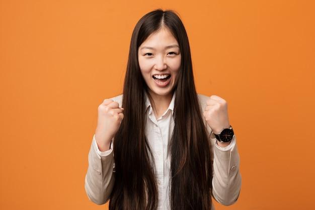 Jonge bedrijfs chinese vrouw onbezorgd en opgewekt toejuichen. overwinning concept.