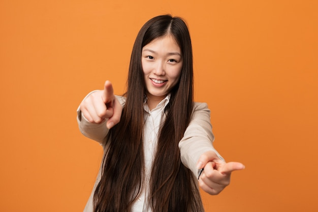 Jonge bedrijfs chinese vrouwen vrolijke glimlachen die aan voorzijde richten.