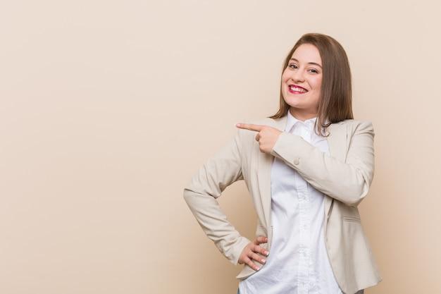 Jonge bedrijfs en vrouw die opzij glimlacht richt, die iets toont op lege ruimte.