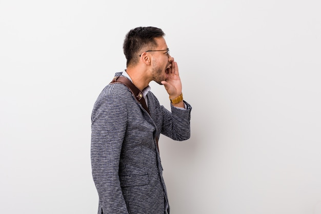 Jonge bedrijfs filippijnse mens tegen een witte muur die en palm schreeuwt dichtbij geopende mond houdt.