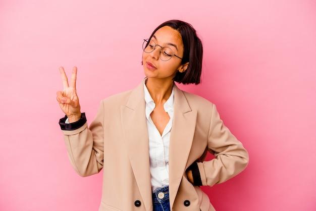 Jonge bedrijfs gemengde rasvrouw die op roze muur vrolijk en zorgeloos wordt geïsoleerd die een vredessymbool met vingers toont