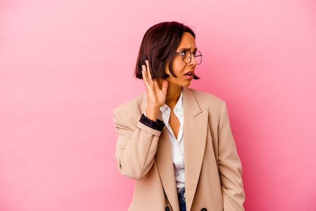 Jonge bedrijfs gemengde rasvrouw die op roze muur wordt geïsoleerd die aan het luisteren van een roddel probeert te luisteren