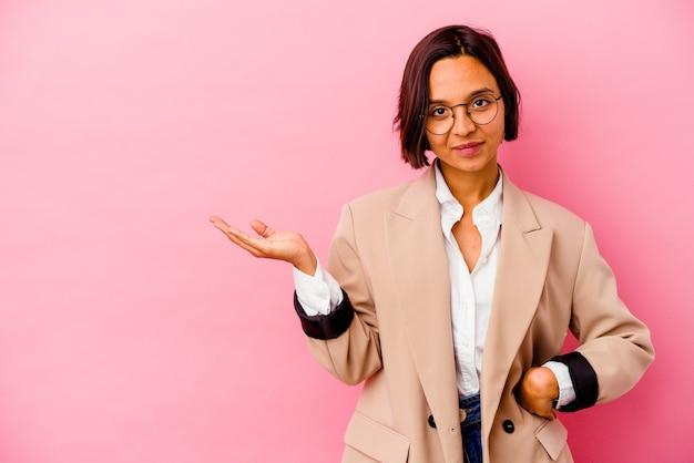 Jonge bedrijfs gemengde rasvrouw die op roze muur wordt geïsoleerd die een exemplaarruimte op een palm toont en een andere hand op taille houdt