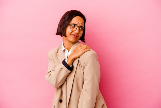 Jonge bedrijfs gemengde rasvrouw die op roze muur wordt geïsoleerd die een schouderpijn heeft
