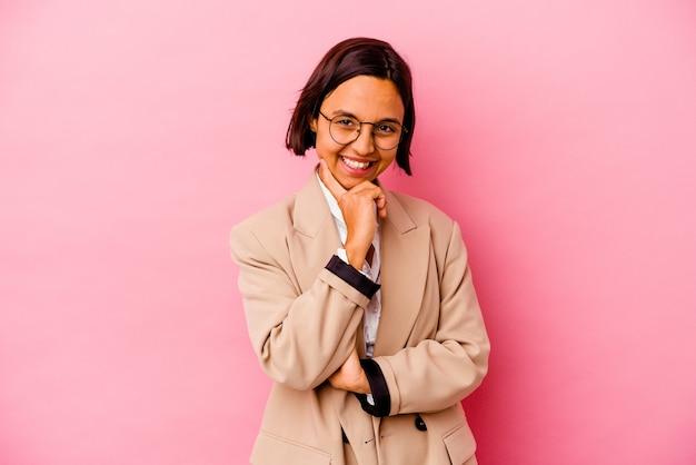 Jonge bedrijfs gemengde rasvrouw die op roze muur wordt geïsoleerd die gelukkig en zelfverzekerd glimlacht, kin met hand aanraakt