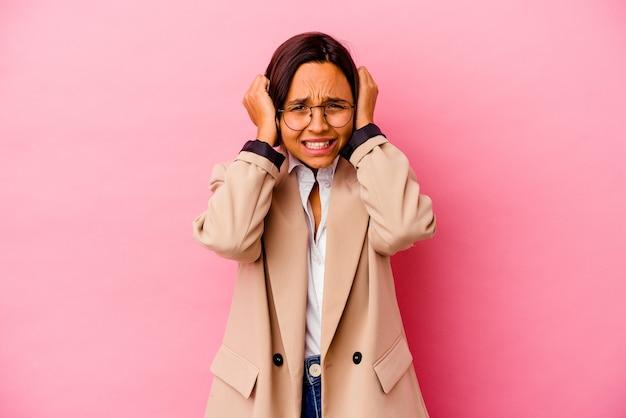 Jonge bedrijfs gemengde rasvrouw die op roze muur wordt geïsoleerd die oren met handen behandelt
